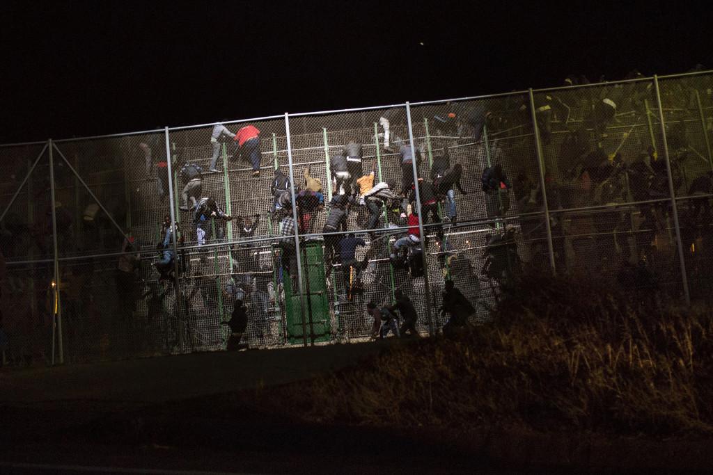 Immigrants salten la triple tanca metàl·lica que separa Nador (Marroc) i Melilla. Foto: Santi Palacios