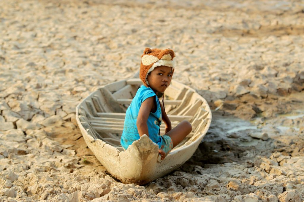 a-girl-sits-on-a-boat-at-a-dried-up-pond-at-the-drought-hit-kandal-province-in-cambodia-on-may-13
