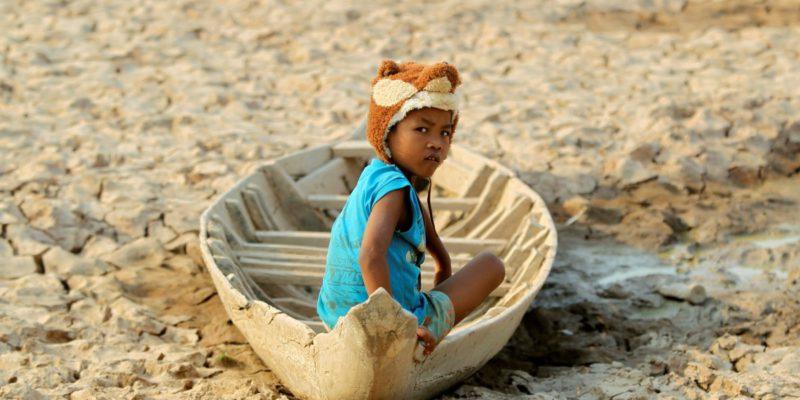 Una nena seu en un vaixell que reposa al fons d'un llac assecat, a Cambodja|Foto: Samrang Pring (Reuters)